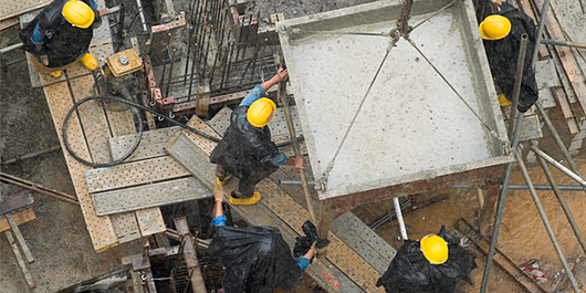 4 workers with hardhats, pouring cement in the rain_600x300_blog