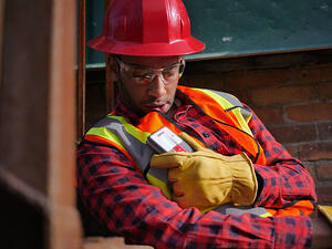 Blackline-Safety-Loner-M6-worker-using-speakerphone-700x525-700x525