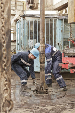Muddy workers on drill rig