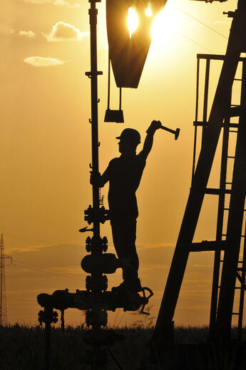 Worker on stack at sunset